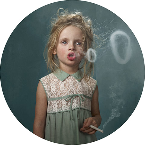 young white girl with blond hair blowing smoke rings