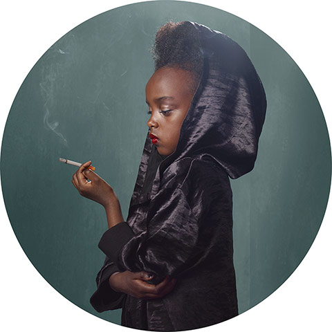 young black girl dressed in black cape smoking a cigarette